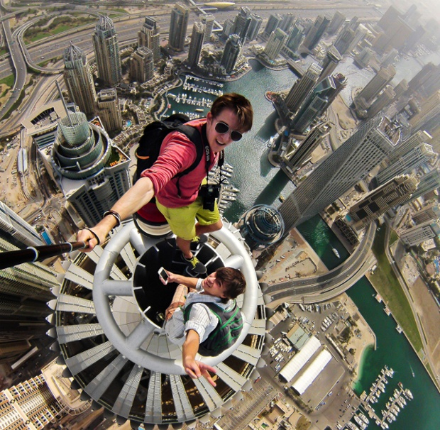 PIC FROM CATERS NEWS - (PICTURED: Daredevils selfie over Dubai) - A RUSSIAN daredevil has captured a vertigo-inducing selfie - while standing on top of a Dubai skyscraper. Nineteen-year-old Alexander Remnev scaled the Princess Tower - the world's tallest residential building at 1,350ft - before getting his camera out to take these stomach-churning pictures. Alexander, who was on holiday in Dubai with friends, says they climbed a number of the city's towering skyline during the course of their stay.
